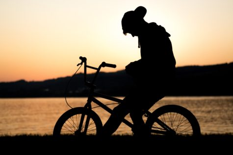 Teen riding bicycle in sunset