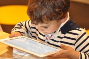 Young boy looking at iPad or tablet