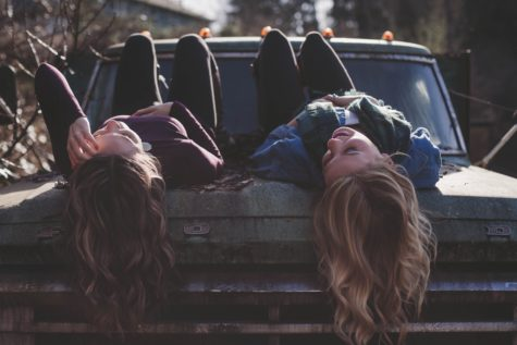Teen or millennial girls laying on car hood