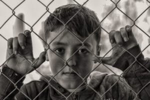 Disadvantaged child behind fence