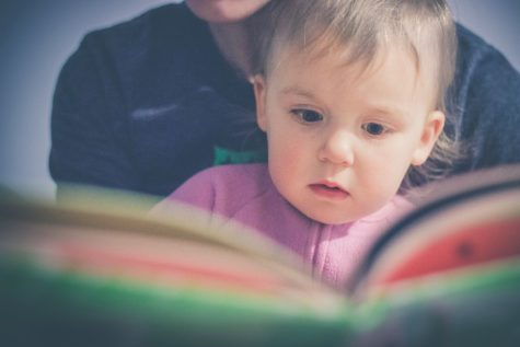 Toddler reading a book with parent