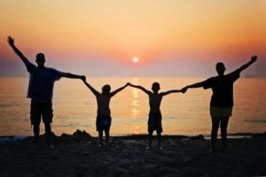 Family on beach vacation at sunset