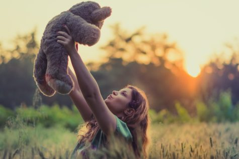 Girl with teddy bear in field