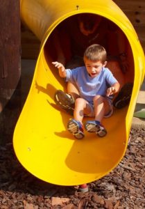 Boy going down playground slide with adult