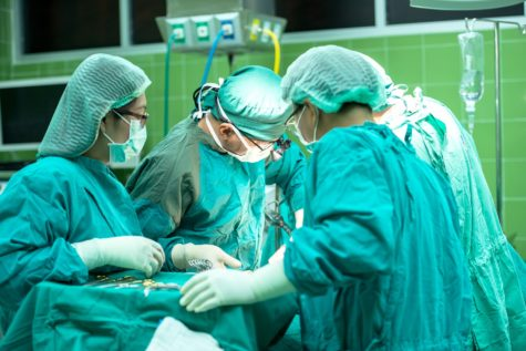 Doctors, nurses performing surgery in operating room