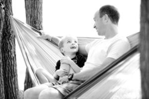 Dad sitting in hammocks with son