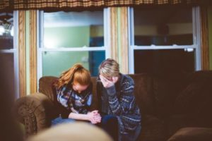Women crying together on couch