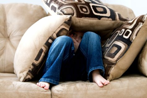 Little boy hiding on couch