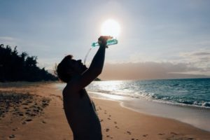 Man drinking water on beach in hot sun