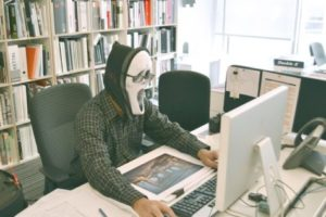 Man wearing Scream mask at office desk