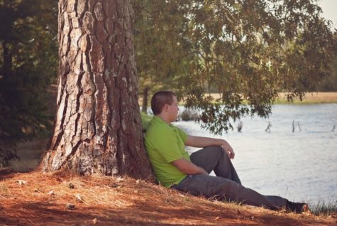 Man sitting alone next to a tree