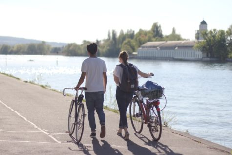 Man and woman walking next to their bicycles