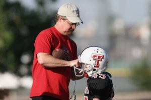 Coach with youth football player