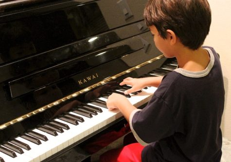 Boy taking piano lesson