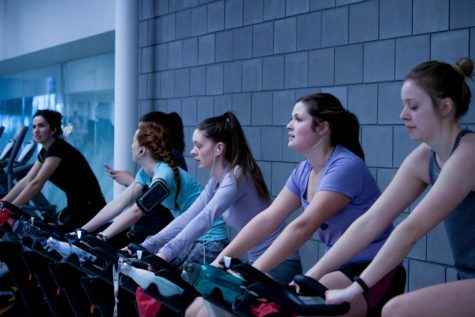 Women on exercise bikes at gym
