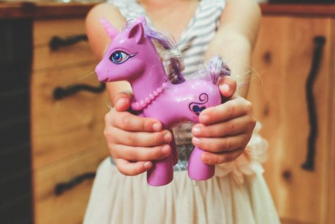 Child holding purple pony toy