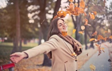 Happy woman throwing leaves