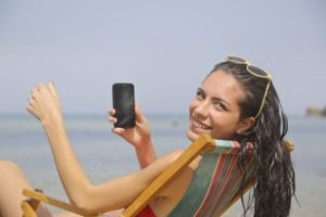 Woman using phone at beach
