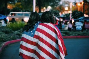 Couple sitting wrapped in US flag