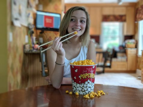 Woman eating popcorn with chopsticks