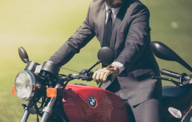 Man in suit riding BMW motorcycle