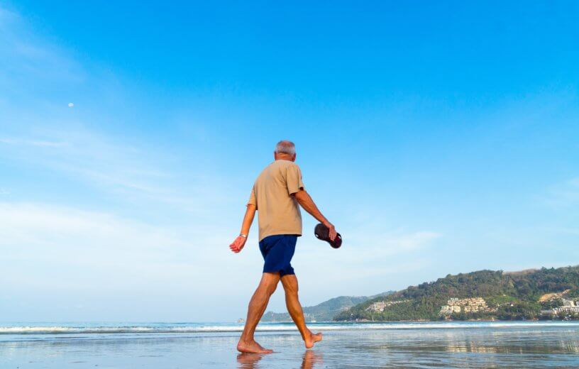 Older man walking on beach
