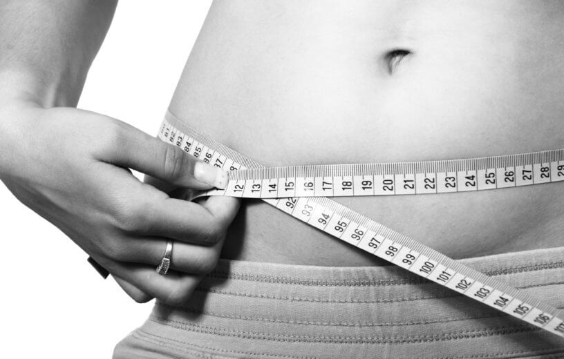 Woman measuring body fat or waist size