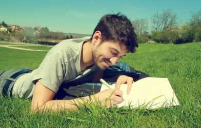 Man lying in grass writing