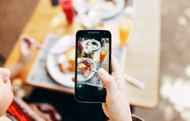 Person snapping photo of food porn with phone