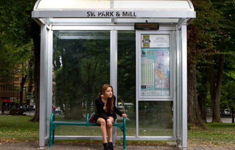 Woman sitting at bus stop