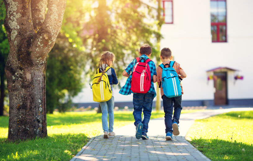 Children walking to school with backpacks on