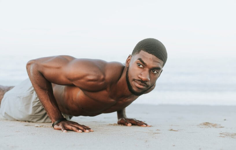 Man doing push-ups on beach