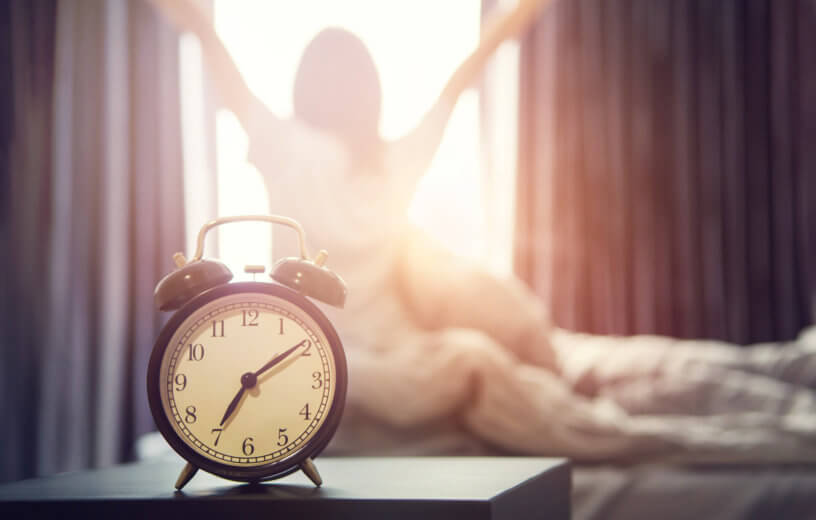 Sleeping woman waking up to alarm clock