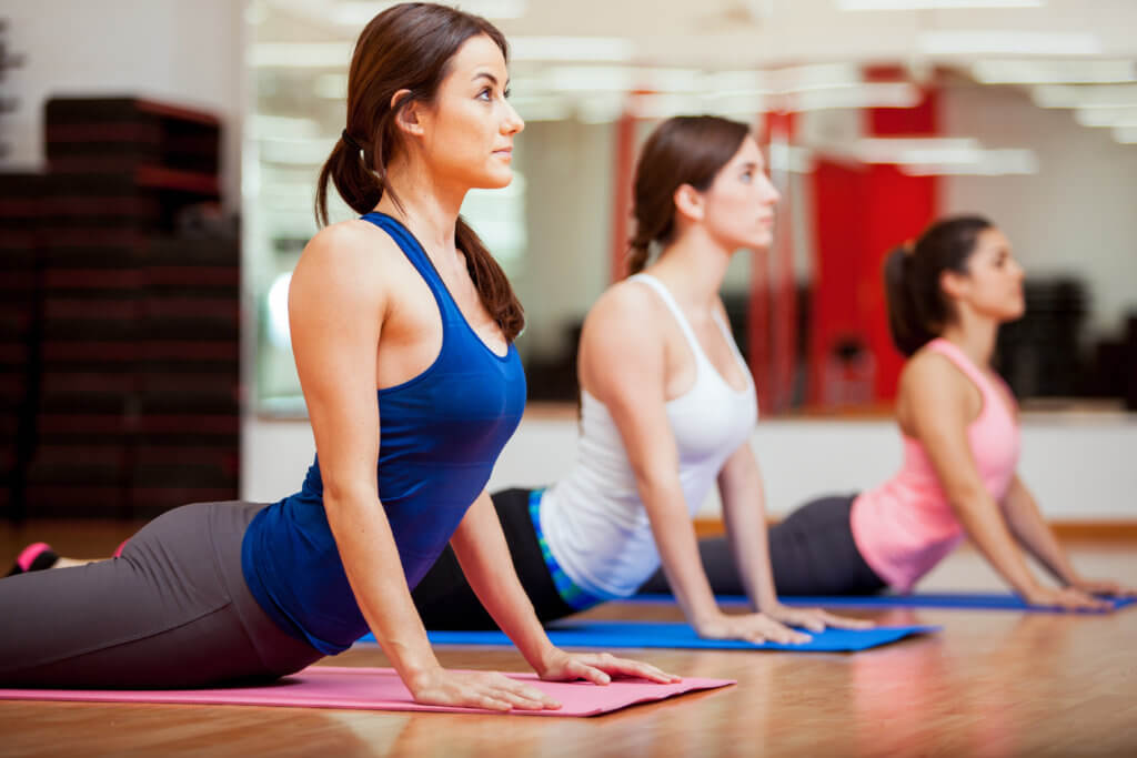 Women working out, doing yoga at gym