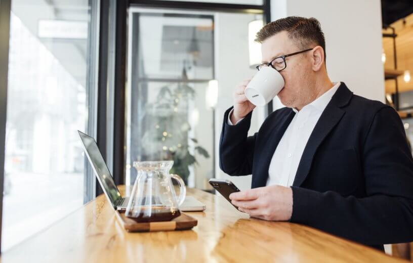Man drinking coffee while doing work
