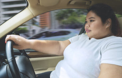 Obesity: Overweight or obese woman driving car
