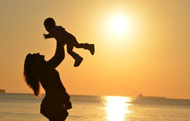 Mother with baby in sunset