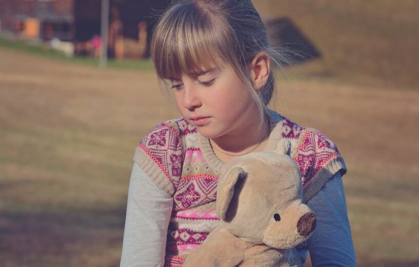 Sad girl holding teddy bear