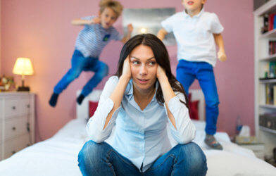 Tired, frustrated mother with children jumping on bed