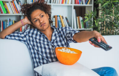 Bored woman sitting at home with remote control watching tv