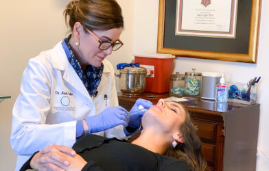 Dr. Anne Taylor administers lip injections to a patient