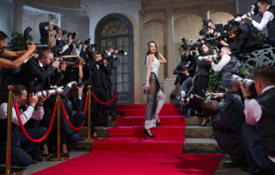 Actress on red carpet with paparazzi