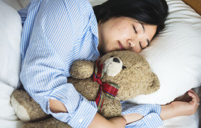 A woman sleeping in bed with a teddy bear