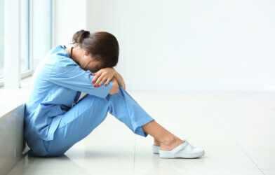 Tired female nurse sitting on floor in hospital