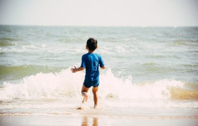 Boy swimming in ocean at beach