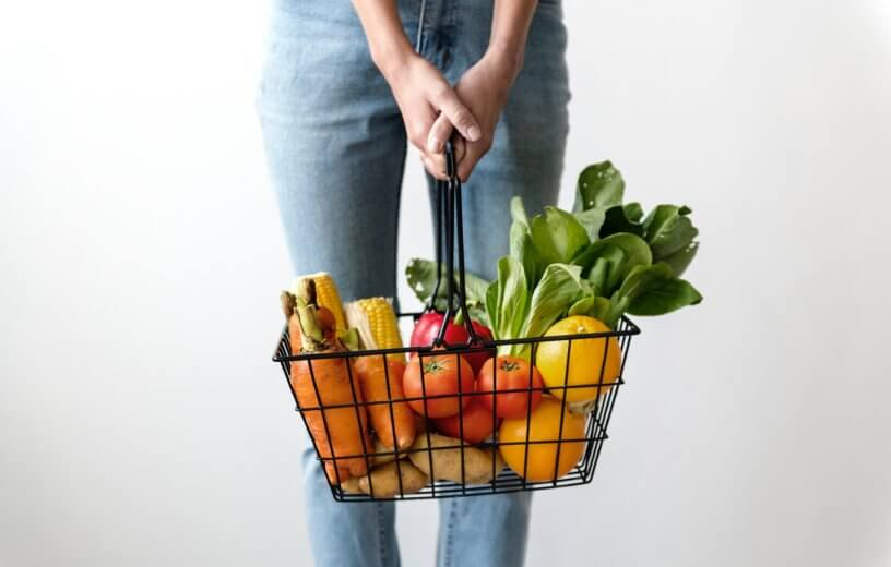 Shopper carrying basket of fresh vegetables