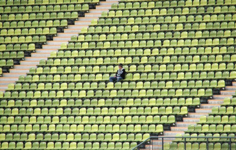 Person sitting alone in college football stadium