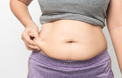 Overweight woman hand pinching excessive belly fat