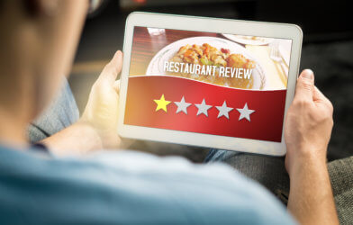 Bad restaurant review. Disappointed and dissatisfied customer giving terrible rating with tablet on an imaginary criticism site, application or website. Man giving one out of five stars at home.