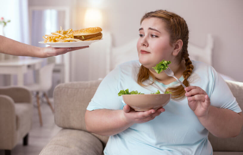 Tasty appealing hamburger enticing obese woman eating salad